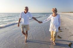 Pares mayores felices que recorren sosteniendo la playa tropical de las manos Foto de archivo