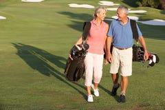 Pares mayores que recorren a lo largo de campo de golf Foto de archivo