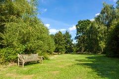 Park Bench in Beautiful Lush Green Garden Stock Photos