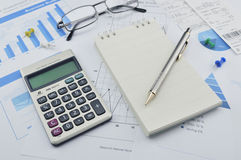 Pen, calculator and notebook on financial chart and graph, accou Royalty Free Stock Images