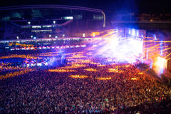 People clapping at night concert, partying and raising hands for the artist on stage. Blurry aerial view of concert crowd Stock Photos
