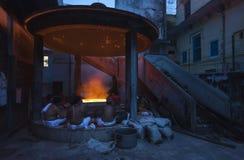 Hindu people sit around fire at night Stock Photo