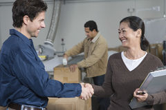People Shaking Hands In Distribution Warehouse Royalty Free Stock Photo