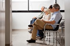 People Waiting For Doctor In Hospital Lobby Royalty Free Stock Photos