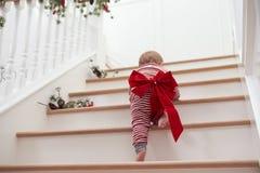 Peuter met Kerstmisboog op Treden in Pyjama's Royalty-vrije Stock Fotografie