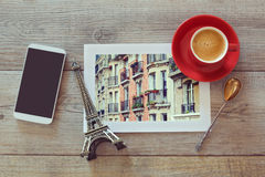 Photo of buildings in Paris on wooden table with coffee cup and smart phone. View from above Stock Image