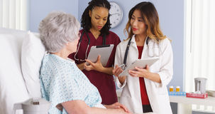 Physician and black nurse speaking with elderly patient in hospital bed Stock Images