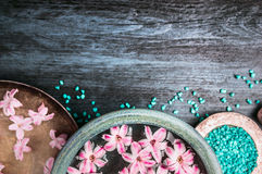 Pink flowers in bowls with water and blue sea salt on wooden table, wellness background, top view Stock Image