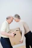 Playful elderly couple moving house Royalty Free Stock Photo