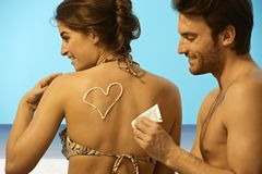 Playful man putting sun cream on woman in swimsuit Royalty Free Stock Photography