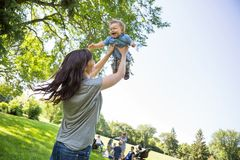 Playful Young Mother Lifting Baby Boy At Park Stock Image