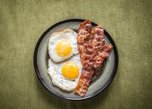 Portion of fried eggs with bacon Royalty Free Stock Images