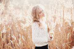 Portrait of a beautiful young blonde girl in a field in white pullover, smiling with eyes closed, concept beauty and health Royalty Free Stock Images