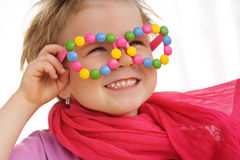 Portrait of cute little girl wearing funny glasses, decorated with colorful smarties, candies Stock Photo