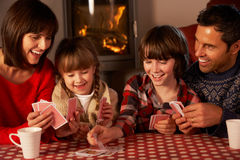 Portrait Of Family Playing Cards By Cosy Log Fire Stock Images