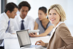 Portrait Of Female Executive Using Laptop With Office Meeting In Background Royalty Free Stock Image