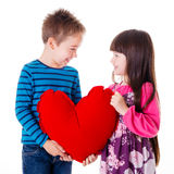 Portrait of girl and boy holding a big red heart shaped pillow Royalty Free Stock Photography
