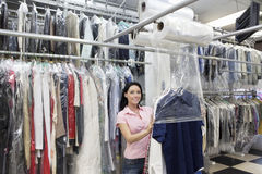 Portrait of a happy mid adult woman putting plastic to dry cleaned clothes in laundry Royalty Free Stock Photos