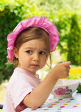 Portrait of little cute girl in a purpule cap eats with appetite a breakfast from a plate with the drawn flower in outdoor cafe Stock Image