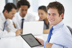Portrait Of Male Executive Using Tablet Computer With Office Meeting In Background Royalty Free Stock Image