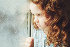 Portrait of a sad child looking out the window. Toning photo. Royalty Free Stock Images