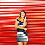 Portrait of trendy stylish girl standing at the red wall backgro Stock Photo