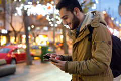 Portrait of young man using his mobile phone on the street at ni Royalty Free Stock Images
