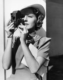 Portrait of a young woman taking a picture with a camera Stock Image
