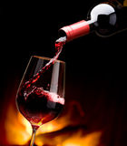 Pouring wine by the fireplace Stock Image