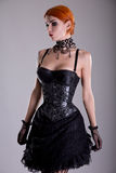 Pretty redhead young woman in silver corset and black skirt Stock Photography