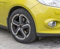 Primo piano giallo dell'automobile - ruota anteriore con l'orlo della lega leggera Fotografie Stock Libere da Diritti