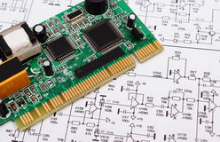 Printed circuit board lying on diagram of electronics, technology Stock Photos