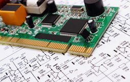 Printed circuit board lying on diagram of electronics, technology Stock Images