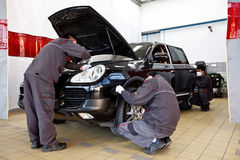 Professional car mechanics working in auto repair service stations. Royalty Free Stock Photography