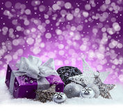 Purple Christmas package , gift of a silver ribbon. Jingle bells , silver christmas balls and christmas stars put on snow. Abstrac Royalty Free Stock Photos