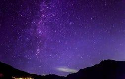 Purple night sky stars. Milky way across mountains Stock Image