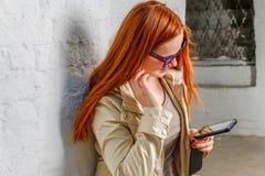 Röd haired kvinna med mobila enheten nära väggen Royaltyfri Bild