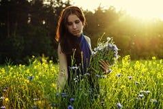 Ragazza che raccoglie i fiori sul tramonto Immagine Stock