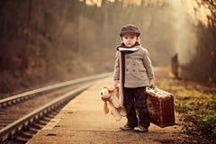 Ragazzo adorabile su una stazione ferroviaria, aspettante il treno Fotografie Stock