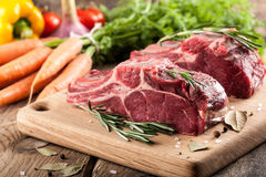 Raw beef meat on cutting board and fresh vegetables Stock Photo