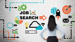 Rear view of the brunette woman who is looking at the wall with colourful icons about job vacancies. Stock Images