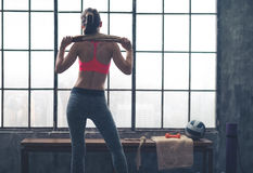 Rear view of fit woman holding towel across shoulders in gym Stock Images