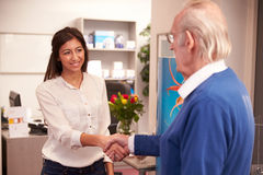 Receptionist Greeting Senior Male Patient At Hearing Clinic Royalty Free Stock Photos