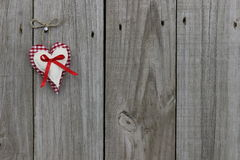 Red gingham and muslin hearts hanging on wood door Royalty Free Stock Photography