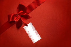 Red Silk Cloth Background with Tag Label and Ribbon Bow, Present Stock Photo