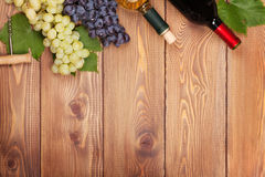 Red and white wine bottles and bunch of grapes Royalty Free Stock Images