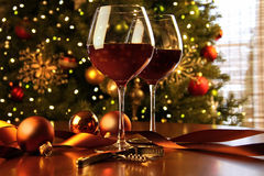Red wine on table with Christmas tree Royalty Free Stock Image