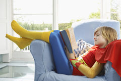 Relaxed Boy In Superman Costume Reading Royalty Free Stock Photography