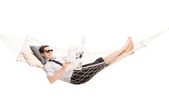 Relaxed man reading newspaper in a hammock Stock Image