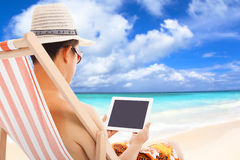 Relaxed man sitting on beach chairs and touching tablet Royalty Free Stock Images